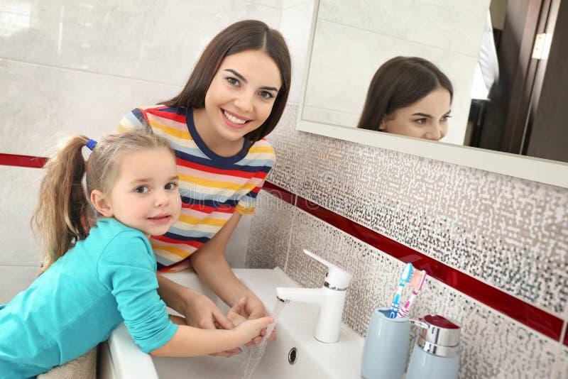 De gelukkige moeder en dochterwas dient badkamers in royalty-vrije stock afbeelding