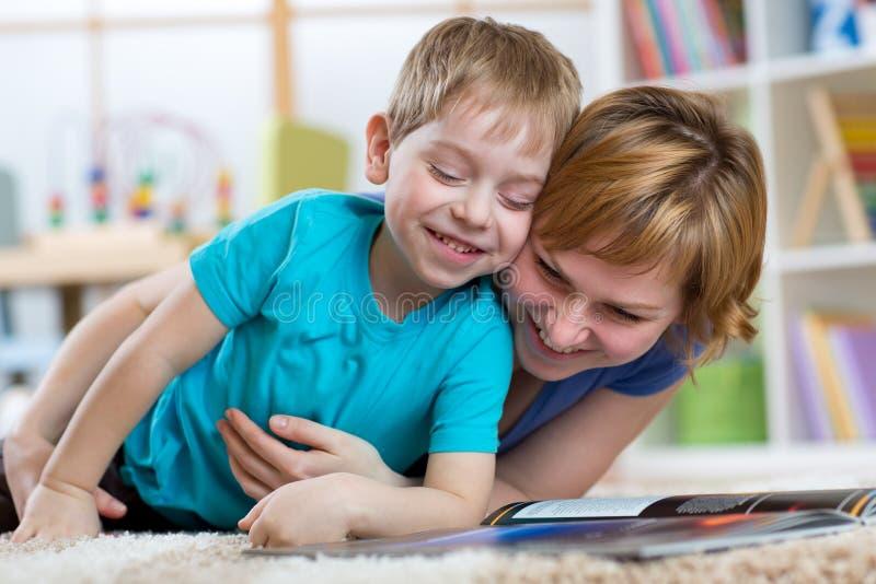 De gelukkige moeder en haar jong geitjezoon brengen samen tijd door stock afbeeldingen