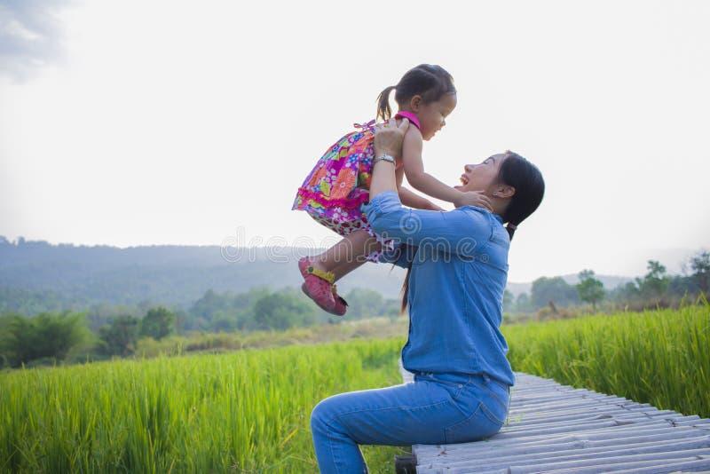 De gelukkige Moeder en haar kind spelen in openlucht het hebben van pret, Groene padieveld achtergrond stock afbeeldingen