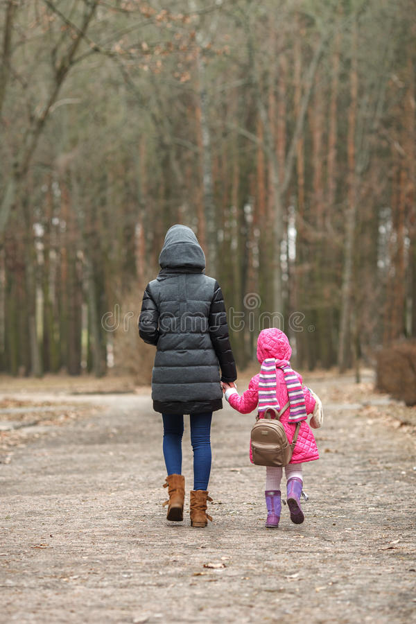 De gelukkige moeder en kinddochterholding overhandigt samen het lopen in de lentepark stock foto's