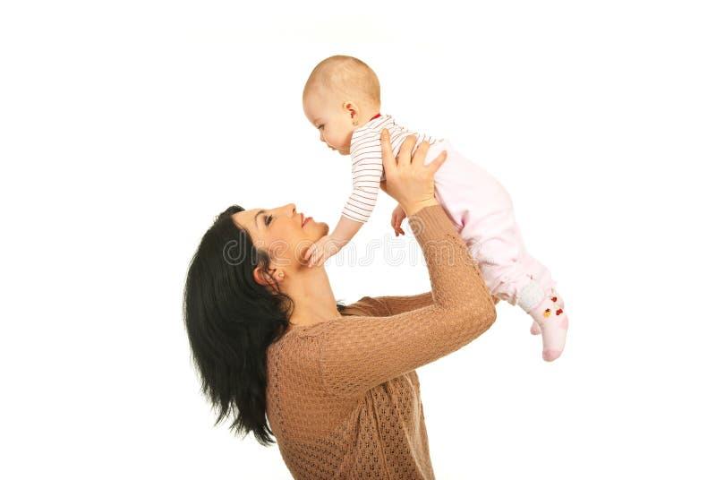 De gelukkige moeder heft haar babydochter op stock afbeeldingen