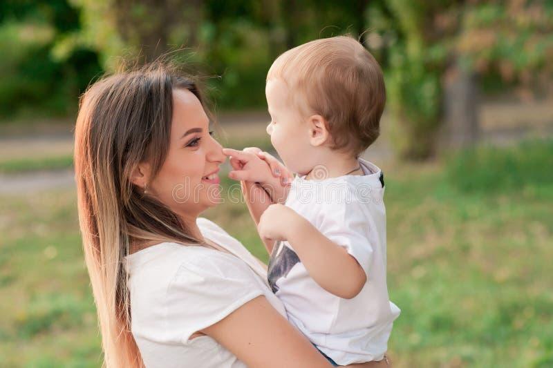 De gelukkige moeder houdt leuke glimlachende zoon in het park stock fotografie