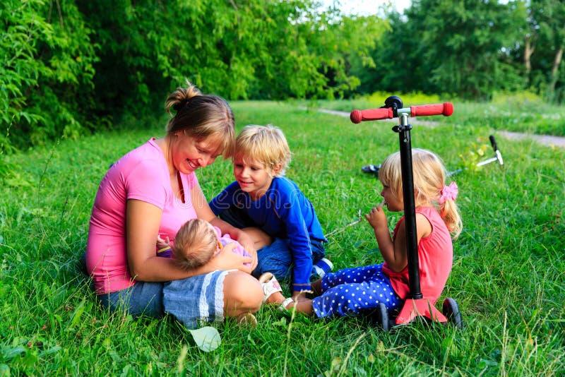 De gelukkige moeder met drie jonge geitjes geniet van zijnd samen in de zomer royalty-vrije stock afbeelding