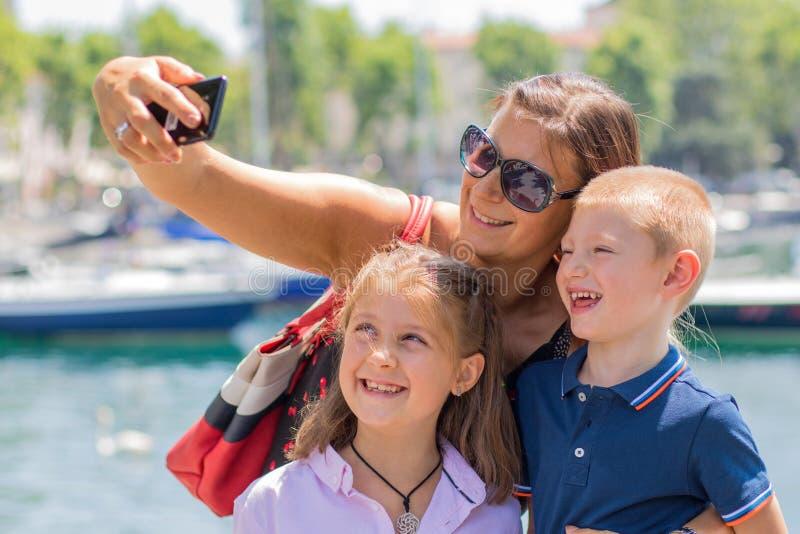 De gelukkige moeder met haar kinderen neemt een selfie in een zonnige dag stock foto