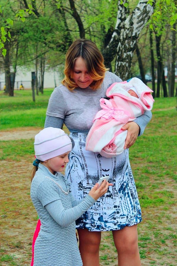 De gelukkige moeder met haar oudere dochter kijkt door de foto van pasgeboren baby stock fotografie