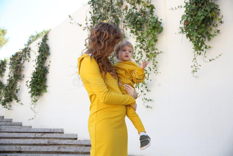 De gelukkige moeder met kind in modieuze klerenfamilie kijkt in een park stock fotografie