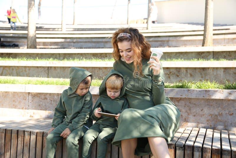 De gelukkige moeder met kinderen in modieuze klerenfamilie kijkt in een park royalty-vrije stock afbeeldingen