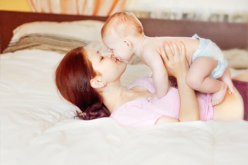 De gelukkige moeder omhelst babyjongen, concentreert zich op moeder stock afbeelding