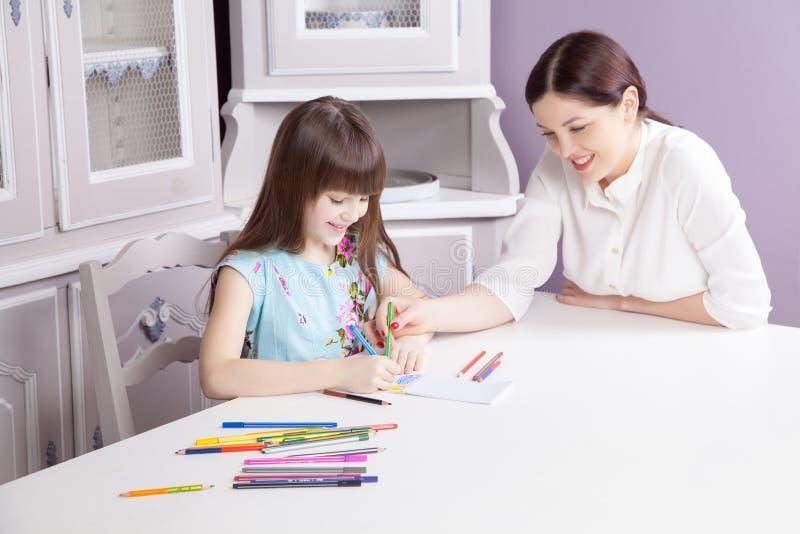 De gelukkige moeder onderwijst haar dochter om te schilderen stock fotografie