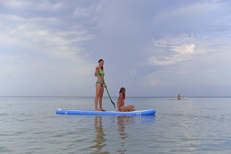 De gelukkige moeder rolt haar dochter op een Raad die voor SAP op het kalme overzees surfen stock foto's
