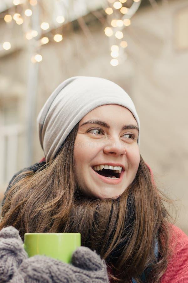 De gelukkige mok van de vrouwenholding met hete drank stock foto