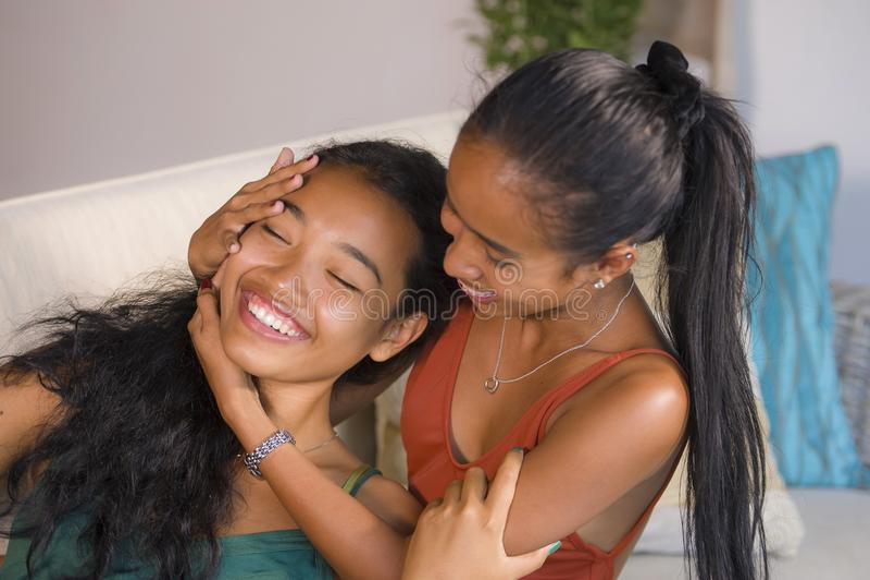 De gelukkige mooie Aziatische vrolijke meisjes koppelen vrolijk thuis lachen samen hebbend de laag die van de pretbank en in wom  stock afbeeldingen