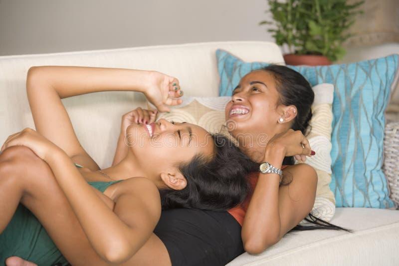 De gelukkige mooie Aziatische vrolijke meisjes koppelen vrolijk thuis lachen samen hebbend de laag die van de pretbank en in wom  royalty-vrije stock foto's