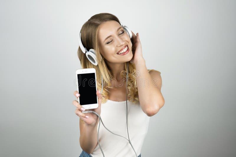 De gelukkige mooie jonge vrouw het luisteren muziek die in hoofdtelefoons smartphone houden isoleerde witte achtergrond royalty-vrije stock afbeeldingen
