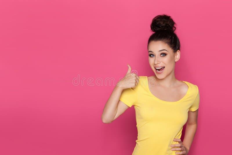De gelukkige Mooie Jonge Vrouw toont Duim en spreekt stock afbeeldingen