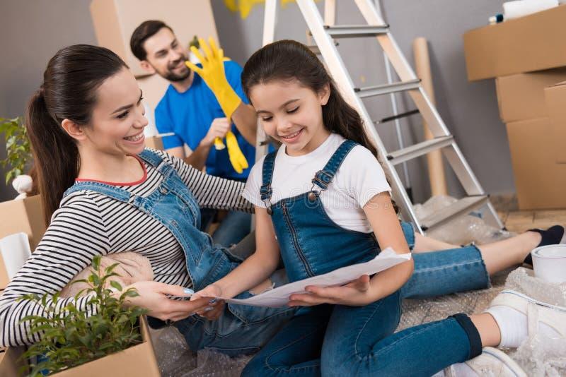 De gelukkige mooie moeder met weinig dochter bespreekt plan voor binnenshuis het schikken van ruimten royalty-vrije stock afbeelding