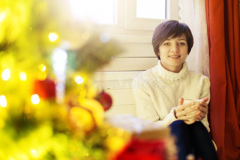 De gelukkige mooie vrouw die hete koffiezitting op venstervensterbank drinken in Kerstmis verfraaide huis stock afbeeldingen
