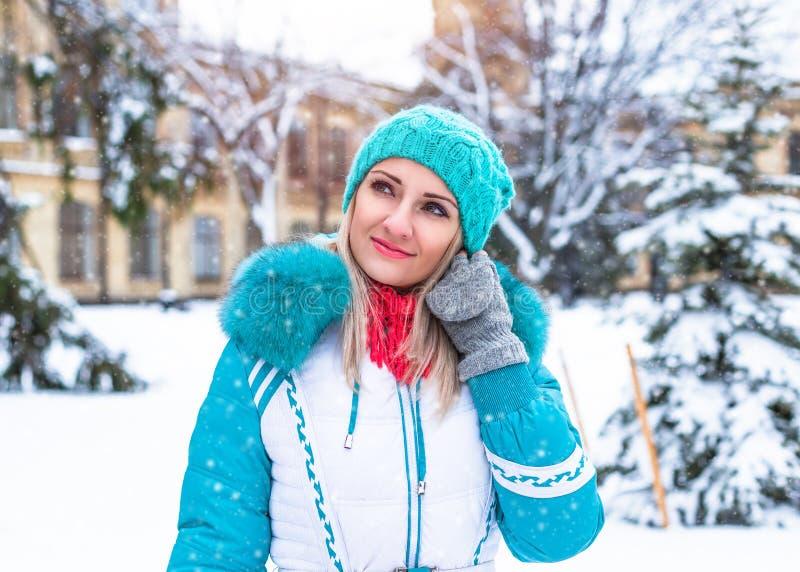 De gelukkige mooie vrouw geniet van sneeuw in de winterpark stock fotografie