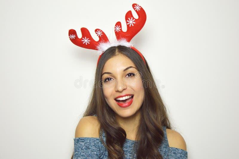 De gelukkige mooie vrouw met rendierhoornen op haar hoofd bekijkt camera op witte achtergrond De vakantie van Kerstmis stock foto