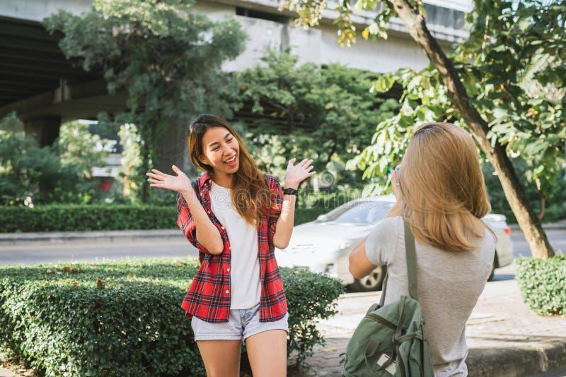 De gelukkige mooie vrouwen van de reizigers Aziatische vriend dragen rugzak Jonge blije vrienden Aziatische vrouwen die camera me stock fotografie