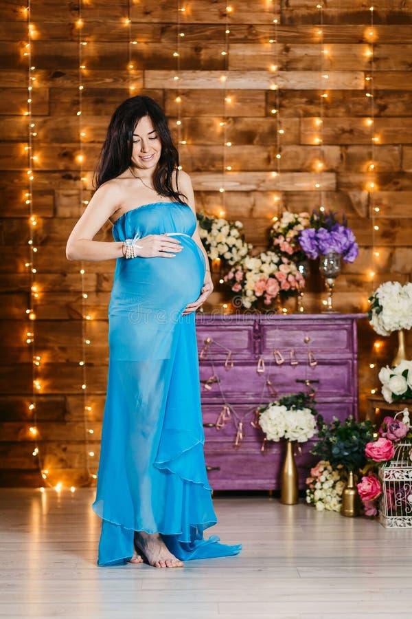 De gelukkige mooie zwangere donkerbruine handen van de vrouwenholding bij haar maag en het glimlachen stock afbeelding