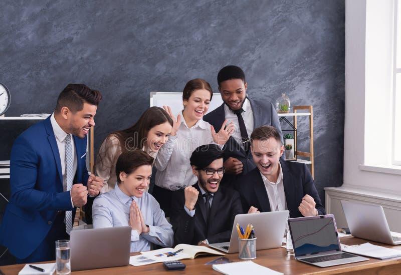 De gelukkige multiraciale managers voltooiden met succes hard project stock foto