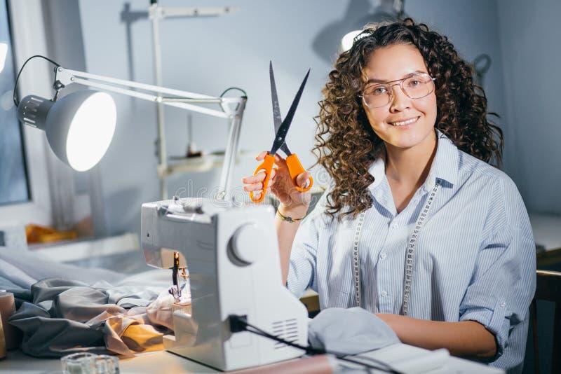 De gelukkige naaister houdt oranje schaar beginnen naaiend proces stock foto's