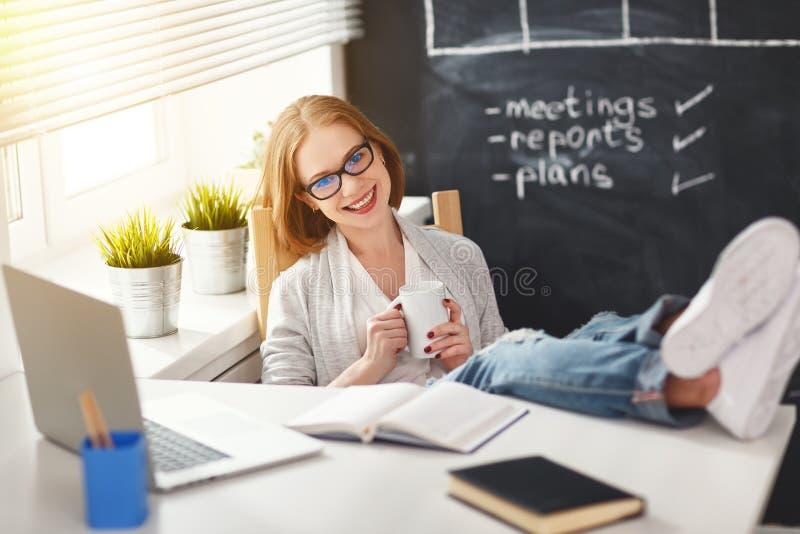 De gelukkige onderneemstervrouw met computer ontspant en rust stock fotografie