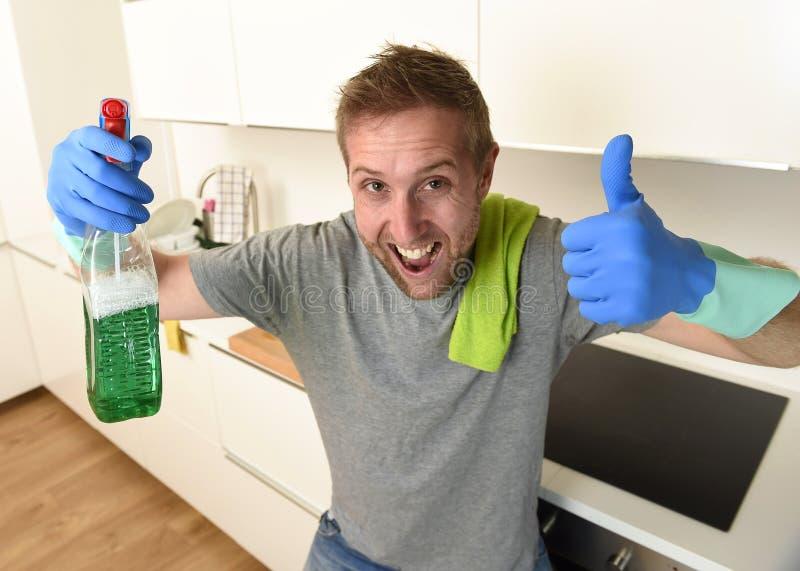 De gelukkige ongeschoren mens in rubberwas gloves het houden van het detergent het schoonmaken nevel glimlachen zeker stock foto's