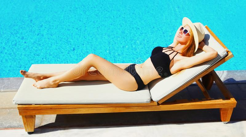 de gelukkige ontspannende jonge vrouw ligt op deckchair over de blauwe achtergrond van de waterpool stock fotografie