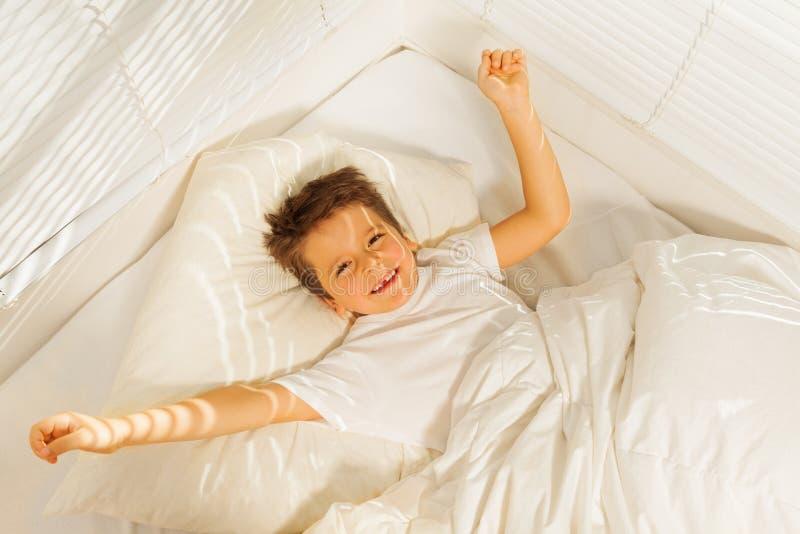 De gelukkige ontwaken van de jong geitjejongen in zijn witte slaapkamer royalty-vrije stock foto's
