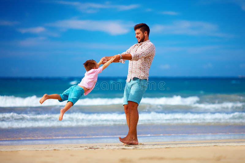 De gelukkige opgewekte vader en de zoon die pret op de zomerstrand hebben, genieten van het leven royalty-vrije stock foto's