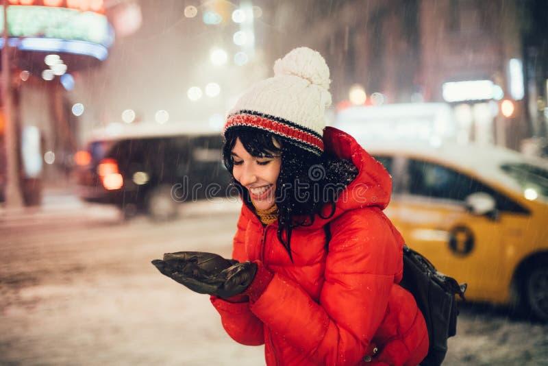 De gelukkige opgewekte vrouw die sneeuwvlokken vangen door palmen en geniet van eerste sneeuw op de straat van de nachtstad stock fotografie