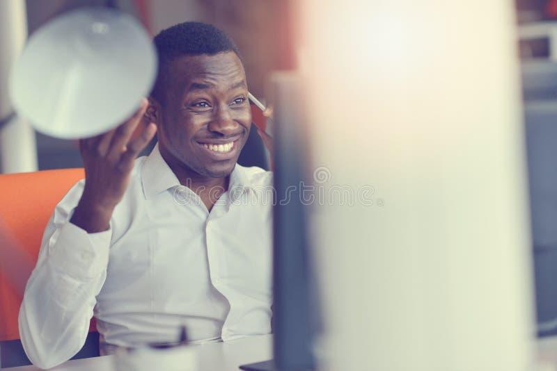 De gelukkige opgewekte zakenman viert zijn succes Winnaar, zwarte mens in bureaulezing op laptop stock afbeeldingen