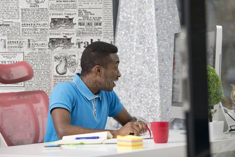 De gelukkige opgewekte zakenman viert zijn succes Winnaar, zwarte mens in bureaulezing op laptop, exemplaarruimte royalty-vrije stock foto's