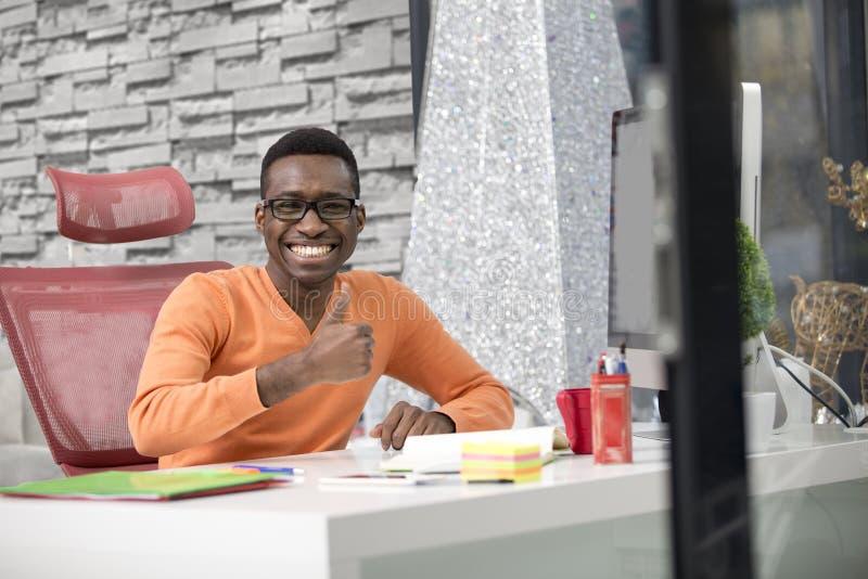 De gelukkige opgewekte zakenman viert zijn succes Winnaar, zwarte mens in bureaulezing op laptop, exemplaarruimte royalty-vrije stock afbeeldingen