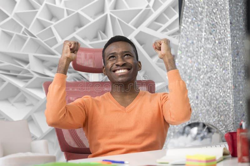De gelukkige opgewekte zakenman viert zijn succes Winnaar, zwarte mens in bureaulezing op laptop, exemplaarruimte stock afbeelding