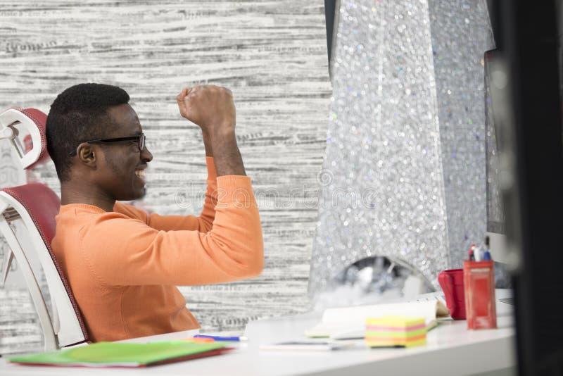 De gelukkige opgewekte zakenman viert zijn succes Winnaar, zwarte mens in bureaulezing op laptop, exemplaarruimte stock fotografie