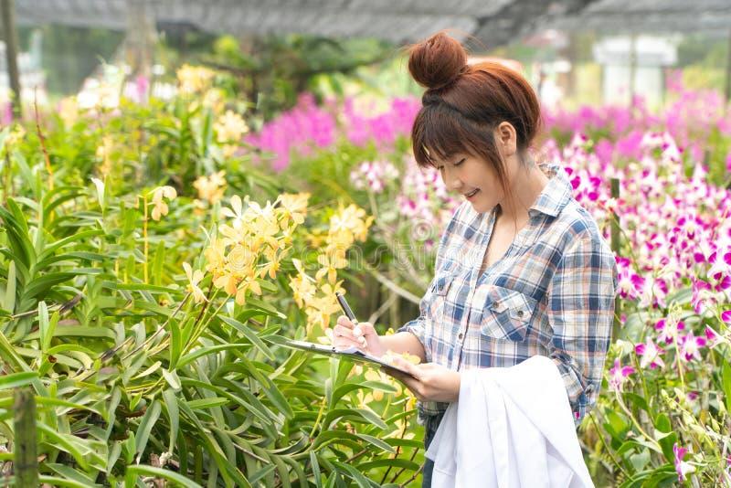 De gelukkige orchidee van het onderzoekers botanische onderzoek een wit GLB en haar hand dragen die een pen houden en notitieboek royalty-vrije stock foto's