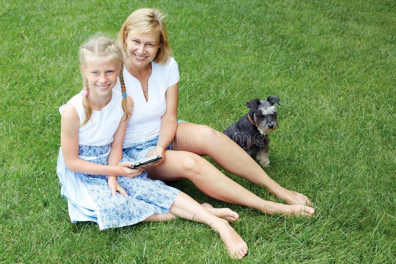 De gelukkige ouder en het kind lezen samen een eBook parenting royalty-vrije stock afbeelding