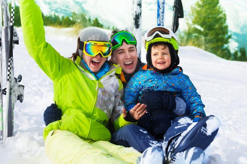 De gelukkige ouders en de jongen met skimaskers zitten op sneeuw stock afbeelding