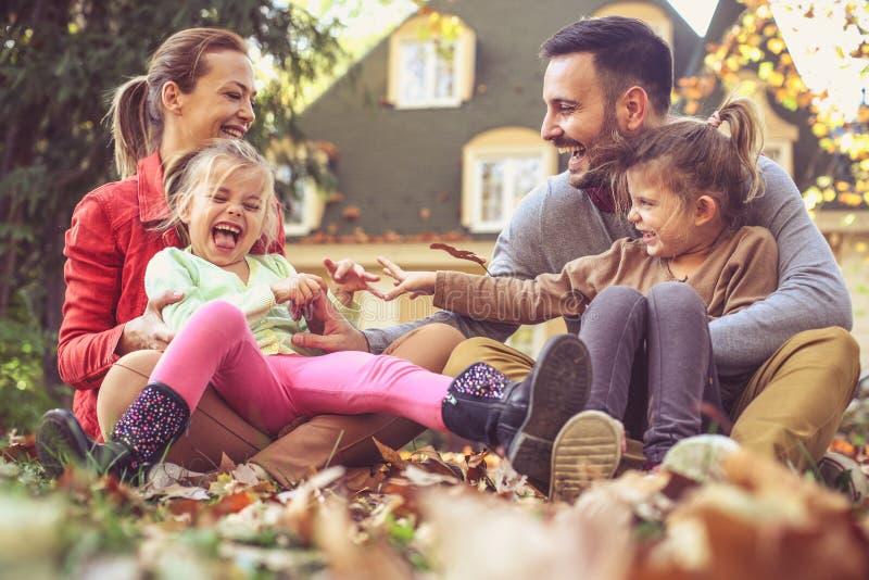 De gelukkige ouders hebben spel met buiten kinderen Het seizoen van de herfst Weg in dalingsbos royalty-vrije stock afbeeldingen