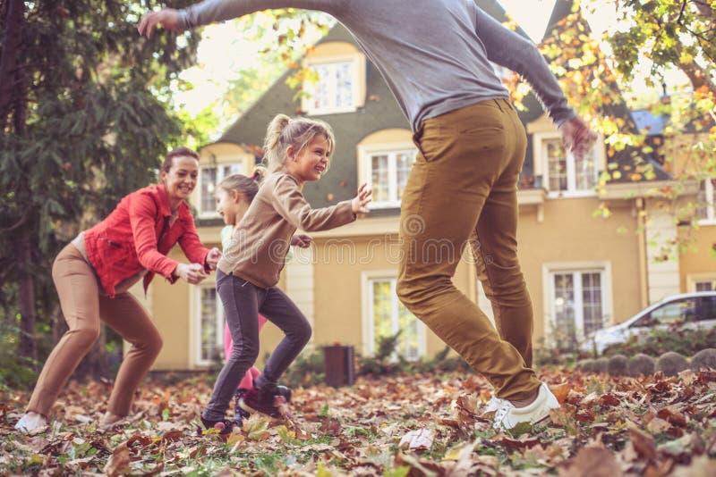 De gelukkige ouders hebben spel met kinderen bij binnenplaats In beweging royalty-vrije stock fotografie