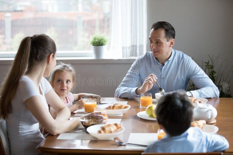 De gelukkige ouders met twee jonge geitjes genieten thuis van gezond ontbijt royalty-vrije stock foto's