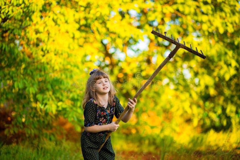De gelukkige ouders van de meisjehulp in tuin met hark Het seizoengebonden tuinwerk stock afbeelding