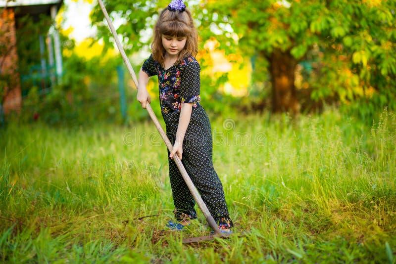 De gelukkige ouders van de meisjehulp in tuin met hark Het seizoengebonden tuinwerk royalty-vrije stock afbeeldingen