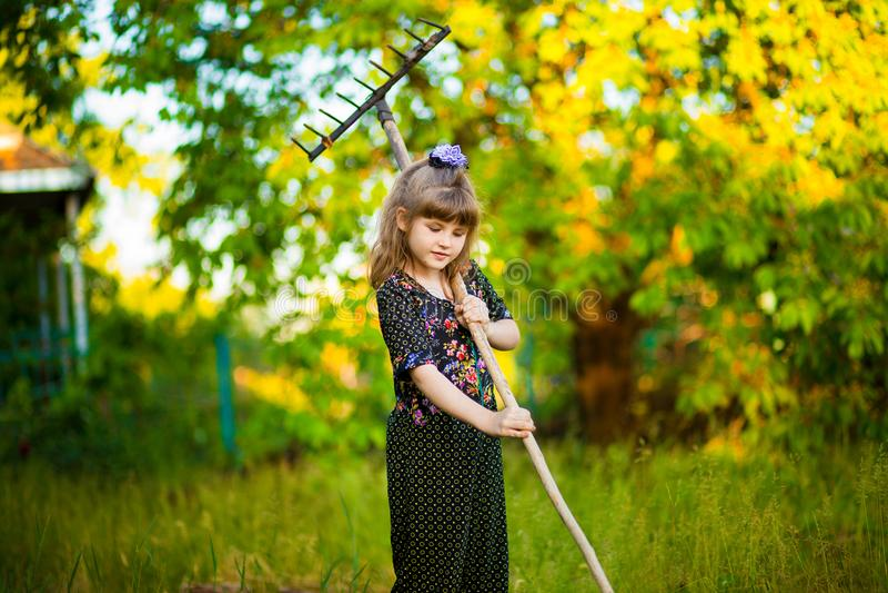 De gelukkige ouders van de meisjehulp in tuin met hark Het seizoengebonden tuinwerk royalty-vrije stock fotografie