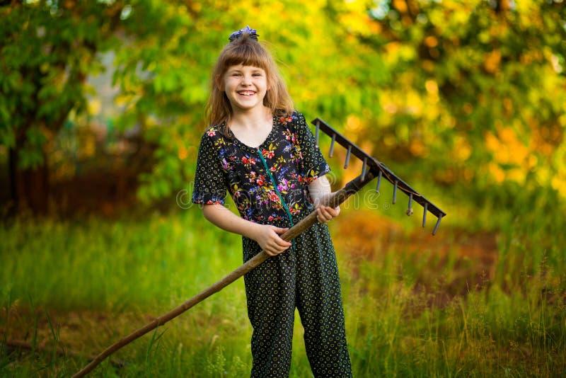 De gelukkige ouders van de meisjehulp in tuin met hark Het seizoengebonden tuinwerk stock afbeeldingen