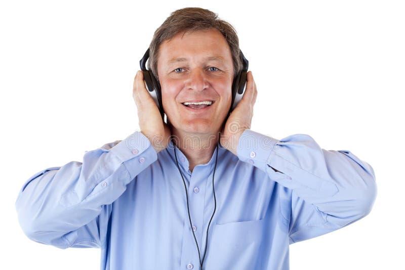 De gelukkige oudste met hoofdtelefoons luistert aan mp3 muziek royalty-vrije stock afbeelding