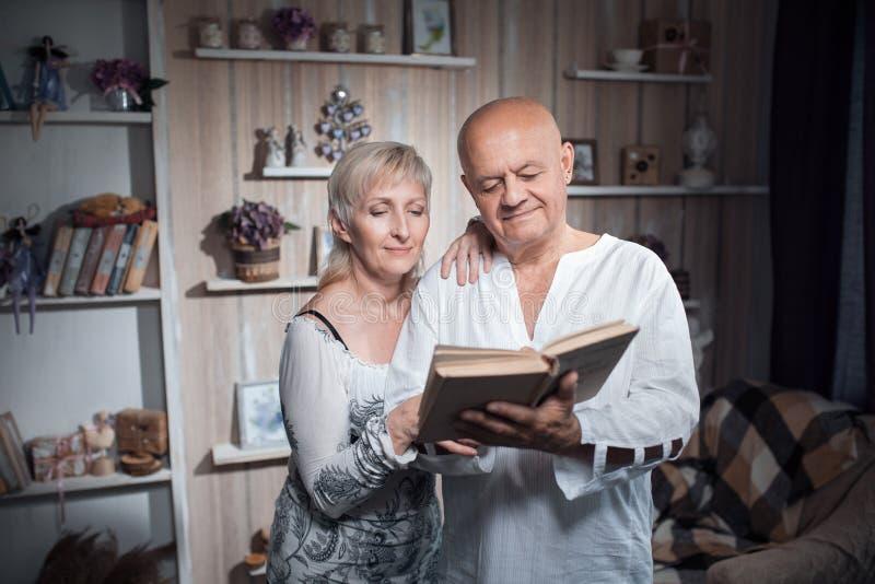 De gelukkige oudsten koppelen greep en lezen boek; royalty-vrije stock afbeelding